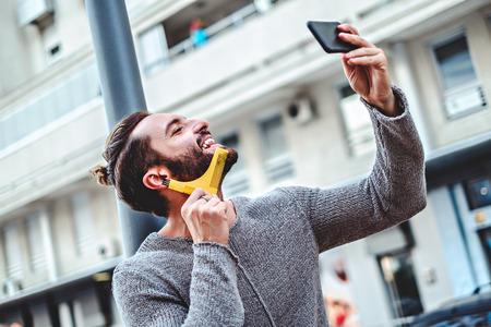 Hipster en el suéter sonriendo y peinar la barba en la calle