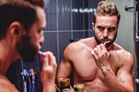 dentalcare: Hipster muscled man brushing teeth in the bathroom Stock Photo