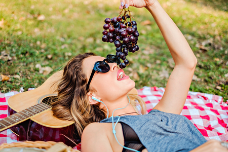 Girl lying and eating grapes in the park while listening music
