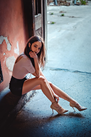 Girl in skirt and high heels sitting on the stairs