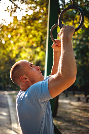Man looking at gymnastics rings in the park and preparing to workout