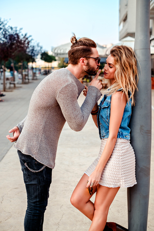 persuading: Man persuading a girl to kiss while she is pulling his sweater Stock Photo