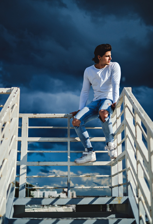Muscled man sitting on the fence while storm is coming. Sun on his face Stock Photo