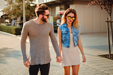 Man trying to cheer up girlfriend while they walking on the street. Beautiful sunny day