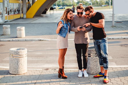 Group of people on the sidewalk looking at mobile phone and smile Фото со стока