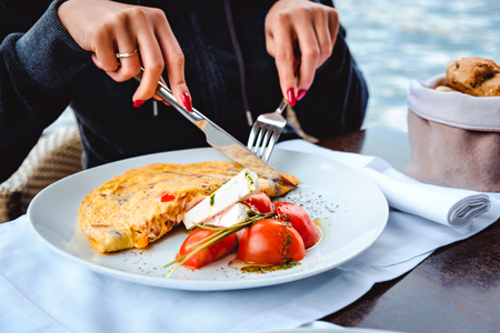 Woman eating scrambled eggs, cheese, tomatto and bread in restaurant by the water