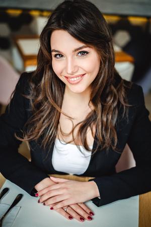 Femme d & # 39 ; affaires souriant dans un restaurant à la recherche de la caméra Banque d'images - 94111805