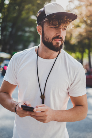 Sad man holding mobile phone outside and looking to the side