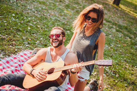 Sexy couple having fun with guitar and laughing on a picnic Stock Photo