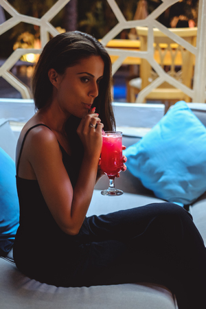 Beautiful young brunette girl sitting in the bar and drinking cocktail
