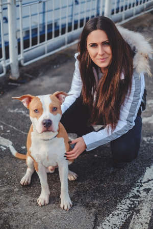 Girl posing outside with her dog on a cold day. Both looking at the camera