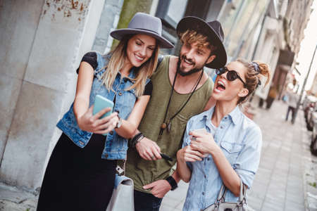Friends taking selfie on the street and laughing. Beautiful summer day