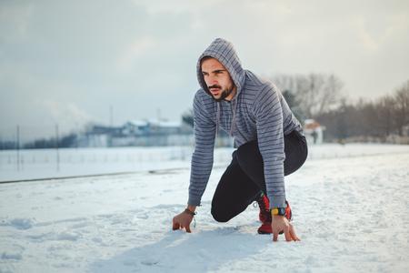 Focused man getting ready to run on a snowy ground