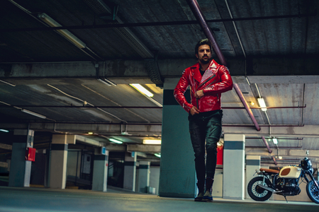 Biker walking from his bike in a garage and button up leather jacket Stock Photo