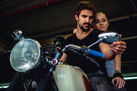 Couple looking at the mirror while sitting on a motorcycle in a garage Stock Photo