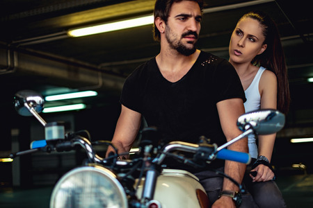 Angry girlfriend talking to her biker boyfriend in a garage while riding a motorcycle Stock Photo