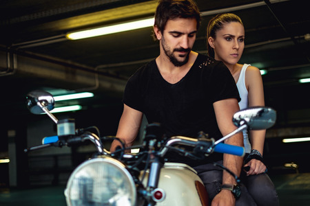 Sad and angry couple sitting on a motorcycle in a garage
