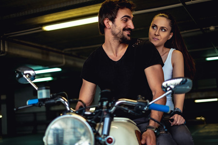 Biker man trying to cheer up his angry girlfriend in a garage