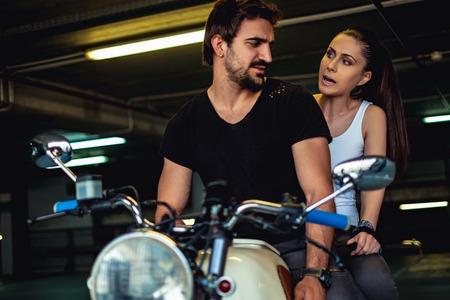 Angry girlfriend yelling at her biker boyfriend in a garage Stock Photo