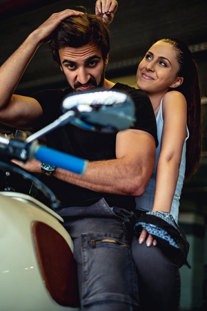 Biker looking into a mirror of his bike while smiling girlfriend is messing up his hair
