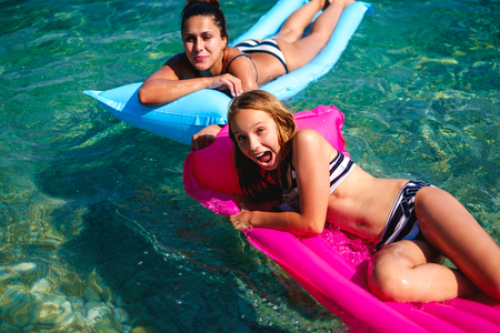 Mother and daughter having fun and tanning on floating beds