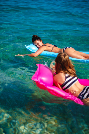 Mother and daughter enjoying while tanning on floating beds Stock Photo