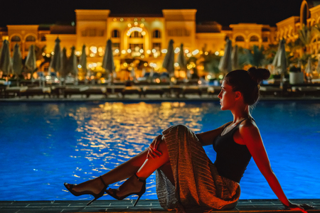 Girl in a dress sitting on the pool edge in the evening Stock Photo