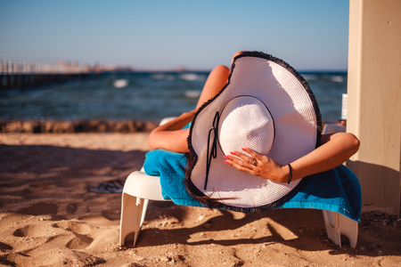 Girl holding hat while lying on the beach and tanning Stock Photo