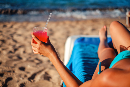 Girl holding cocktail while lying in swimwear on the beach and tanning