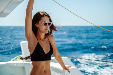Beautiful girl standing on a boat and holding on while sailing on waves Stock Photo