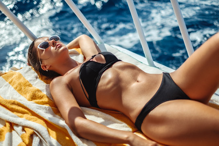 Beautiful girl tanning on a boat deck while sailing on waves Stock Photo
