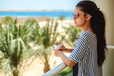 Beautiful girl enjoying cup of coffee on a balcony with sea view in the background Stock Photo