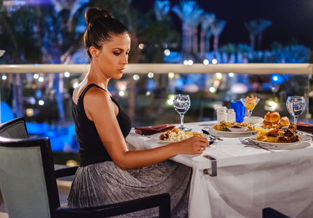 Elegant girl sitting at the restaurant table and looking sadly down to the ground Stock Photo