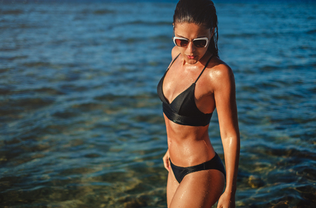 Wet girl with sunglasses standing in the sea water and looking down