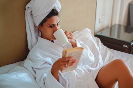 Girl drinking coffee and reading a book while lying in the bed Stock Photo