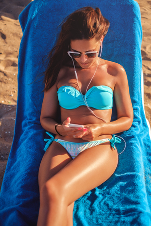Girl listening music on headphones while looking on the phone and tanning on the beach Stock Photo