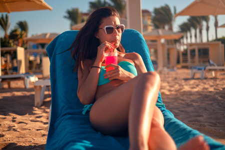 Beautiful girl drinking cocktail while lying on the beach and looking far away