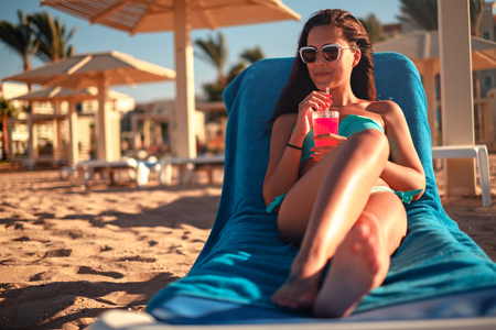Beautiful girl smiling while drinking cocktail on the beach and looking far away Stock Photo