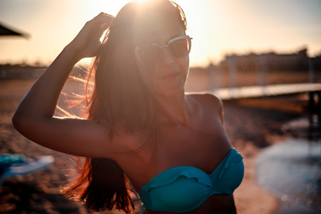 Girl smiling and posing against the sun on a beach