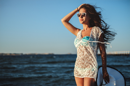 Girl holding her hair an hat while standing on a windy beach Stock Photo