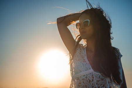 Girl holding her hair and posing in front of the sun