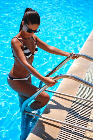 Serious brunette entering swimming pool by stairs