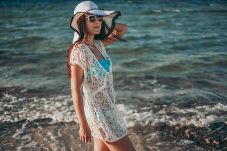Girl smiling while standing on the windy beach and holding her hat Standard-Bild