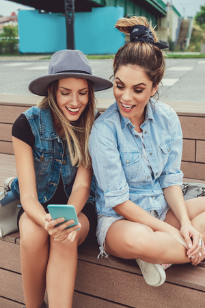 Girlfriends looking at mobile phone and smiling while sitting outside