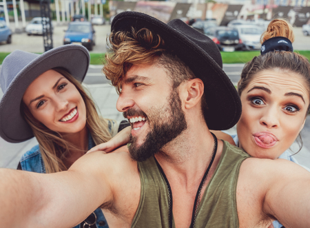 Friends making faces while taking selfie outside Stock Photo
