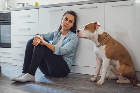Sad woman sitting on a kitchen floor and looking at her dog Stock Photo