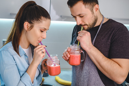 Young couple drinking smoothie with a straw in the kitchen and smiling Stock Photo