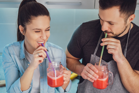 Young Couple laughing while drinking smoothie in the kitchen Stock Photo