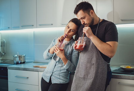 Wife leaning gently on her husband in the kitchen while drinking smoothie