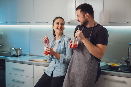 Husband and wife having fun with smoothie in the kitchen and looking at each other